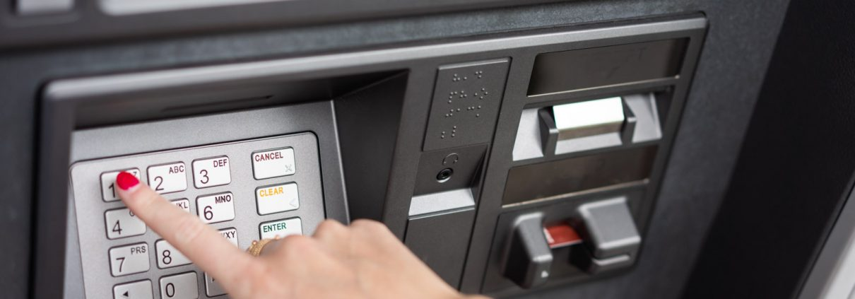 A customer's hand inserting a debit card into an ATM machine