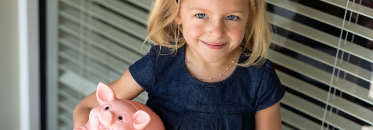 Girl holds piggy bank