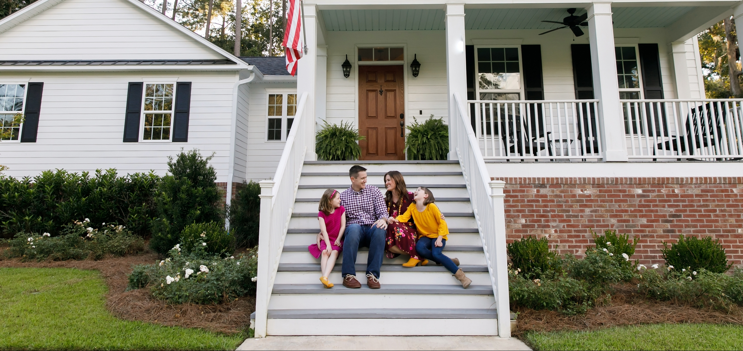 Family standing outside front of new construction white siding farmhouse in the suburbs